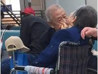 老爺爺細語安慰輪椅上生病的老伴 她抬手觸摸他的臉頰