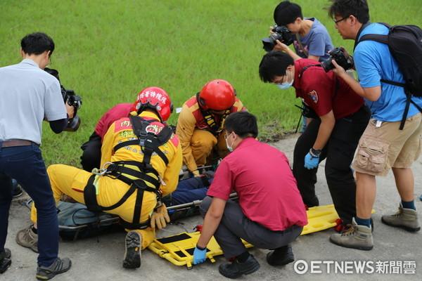 搜救人員以黑鷹直升機將李明翰吊掛救出後,躺在擔架上由消防人員送往慈濟醫院急救。(圖/記者王兆麟攝)