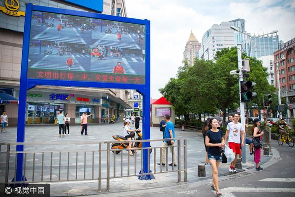 ▲▼南京市新街口裝置臉部辨識設備,會拍攝行人闖紅燈的身影,並在公共螢幕上顯示。(圖/CFP)