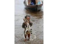 年紀小但愛心大!男孩背狗、女孩抱樹懶涉水避難